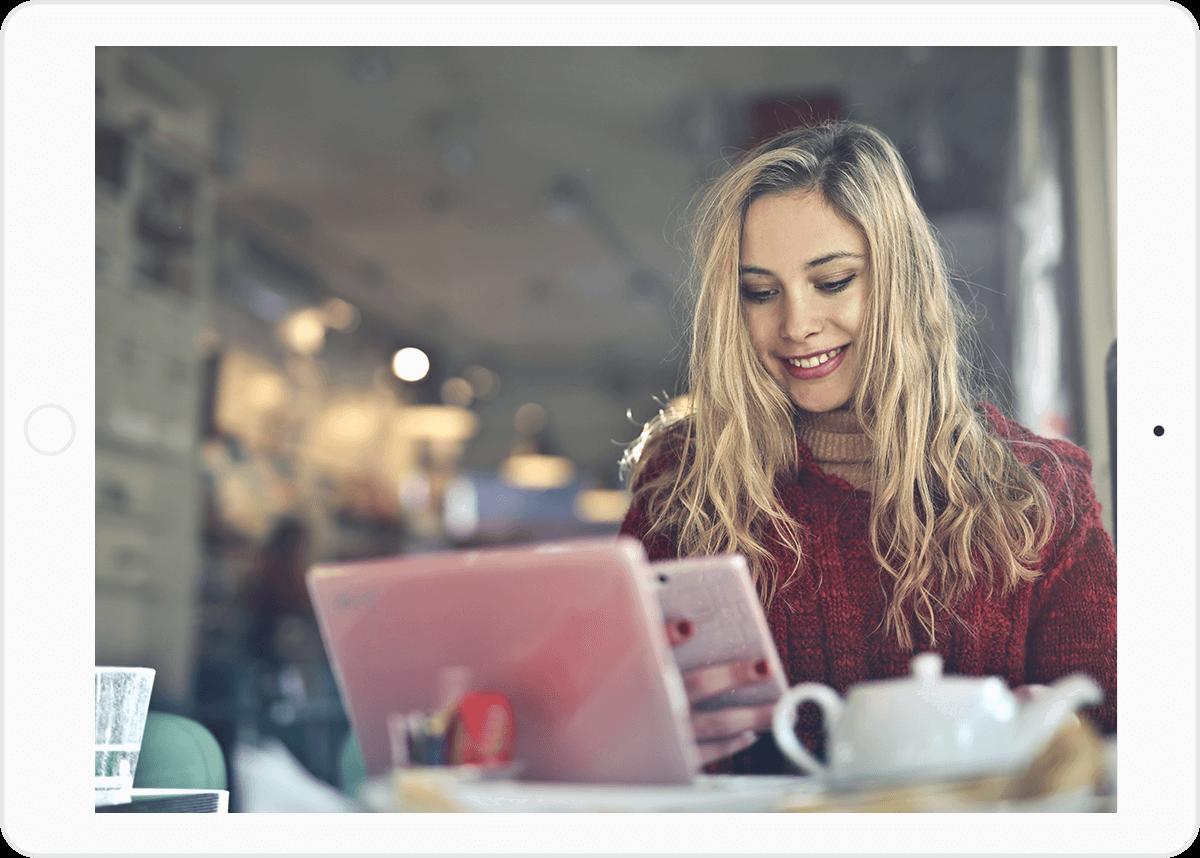 CAIRON Kommunikationslösungen: Junge blonde Frau mit einem roten Pullover in einem Cafe mit Handy in der Hand