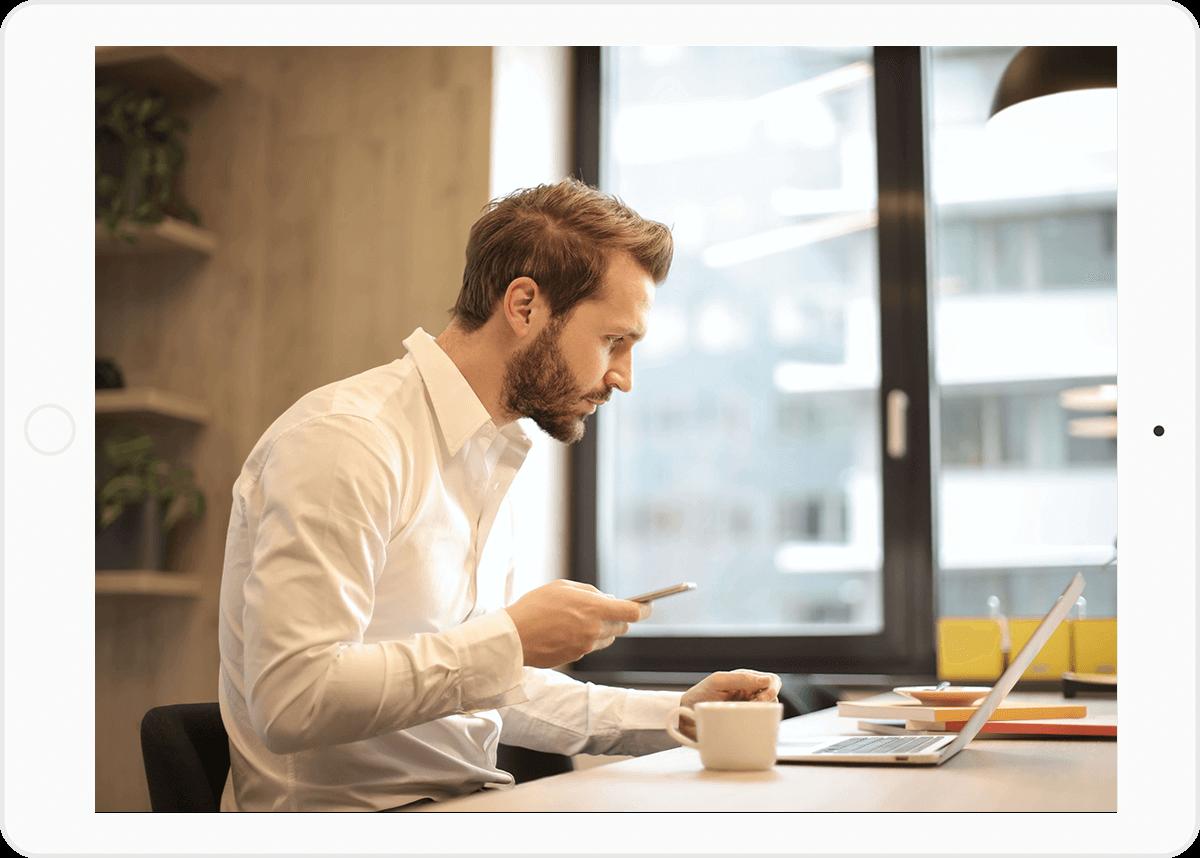 CAIRON Kommunikationslösungen: Junger blonder Mann im Business Look mit Handy in der Hand und Blick auf den Laptop