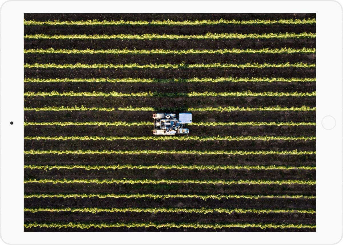 Image of a tablet showing the top view of an agricultural field with a tractor in the center as an example of a possible application of the IoT